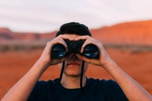 A man in Arizona looking through binoculars.