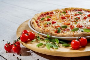 A pizza on a wooden plate you can try after moving to New Jersey with teenagers.