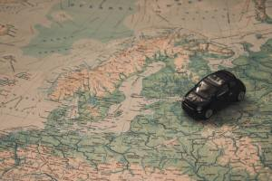 There is a map and a small black toy car on the map.