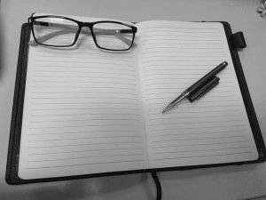 A notebook, a pen, and a pair of glasses to organize a move across town properly.