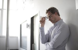 A stressed-out person holding glasses while leaning on a wall.