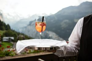 A waiter carrying a glass on a tray.