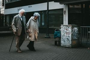 An elderly couple taking a walk and discussing moving from Arizona to New Jersey.