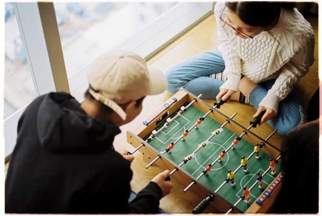 A man and a woman playing table football as a way to motivate your employees to return to office