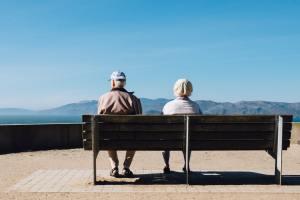 Two seniors aitting on a bench.