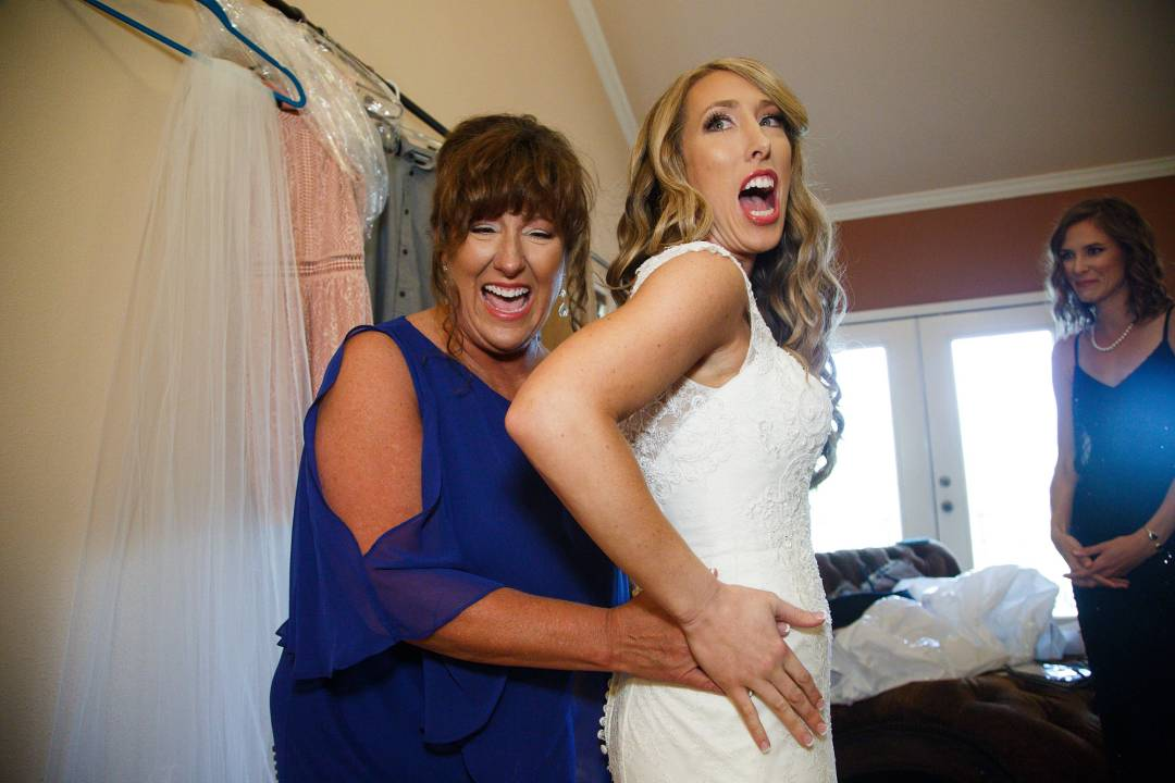 Antebellum Oaks Wedding - Austin Wedding Photographer - Jacob and Katie - bride and mom putting wedding dress on -