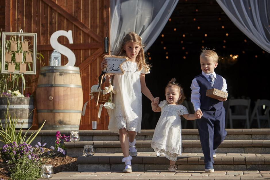 Flower girls and ring bearer walk into the golden hour wedding ceremony.