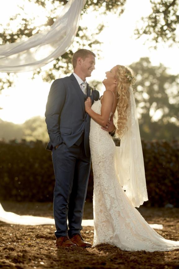 Bride laughs during couples wedding portraits.