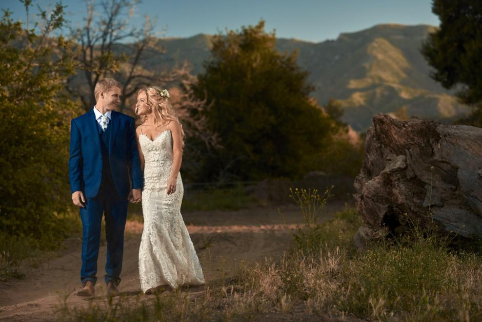 Bride and groom hold hands and walk back after golden hour wedding portraits.