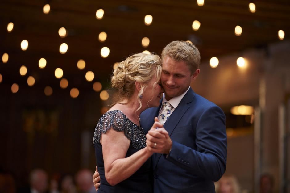 Mother and Groom dance under twinkling lights.