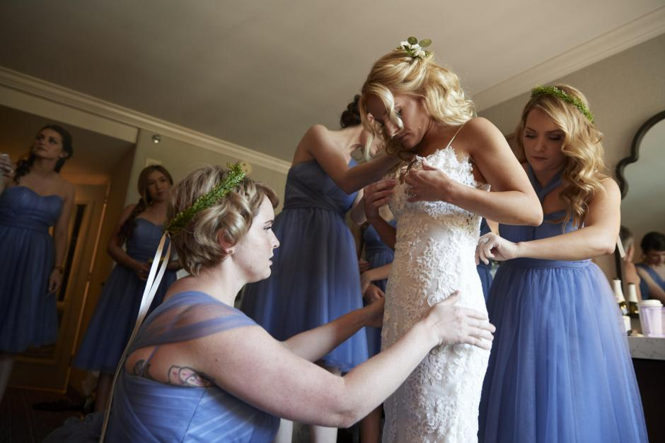 Sisters and brides maids help bride put on her dress.