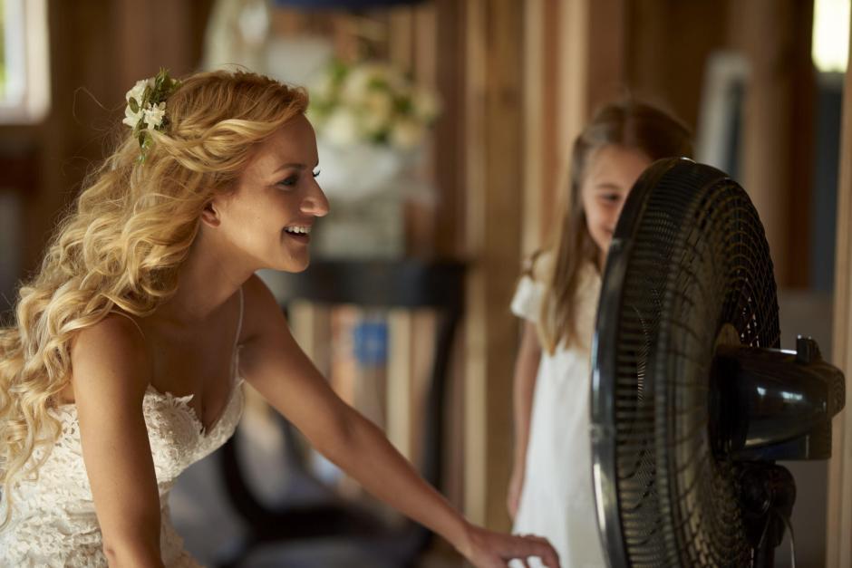 Bride drying tears of joy in front of a fan.