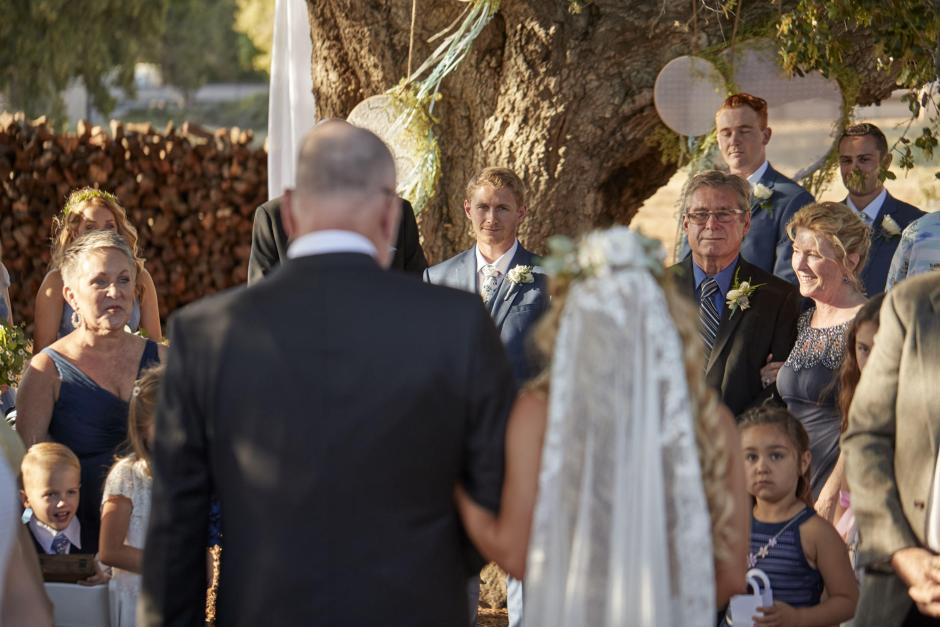 Dad walks bride down the isle as the groom waits during the golden hour wedding.