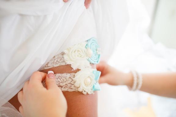 Bride putting on garter belt.