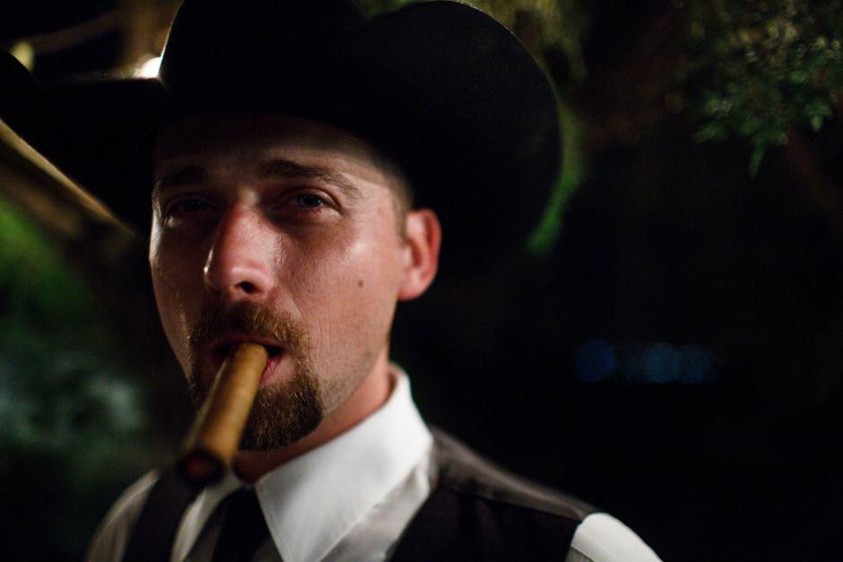 Groom enjoying a cigar outside TerrAdorna in Manor, Tx