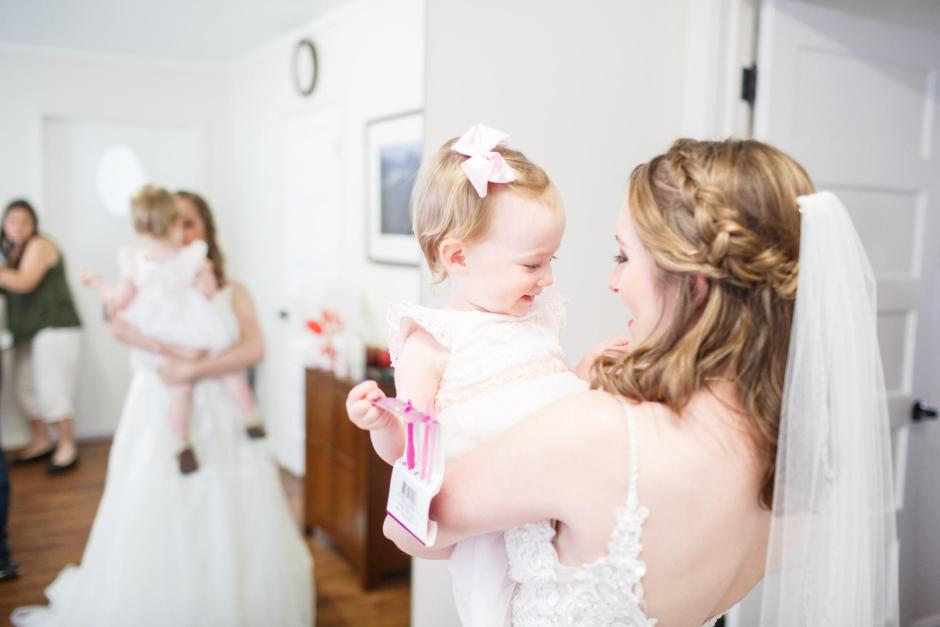 Joshua and Brittany Wedding - Bride holding a cute flower girl before her wedding at Hyde Park Presbyterian Church in Austin, TX.