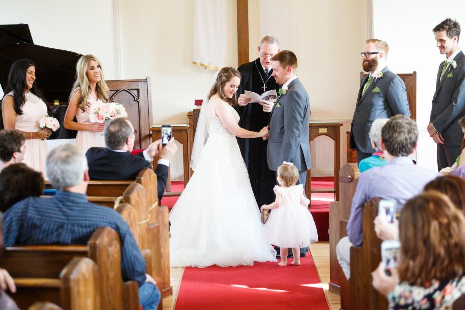 Joshua and Brittany Wedding - A cute flower girl interrupts the ceremony to hand the bride something at Hyde Park Presbyterian Church in Austin, TX.