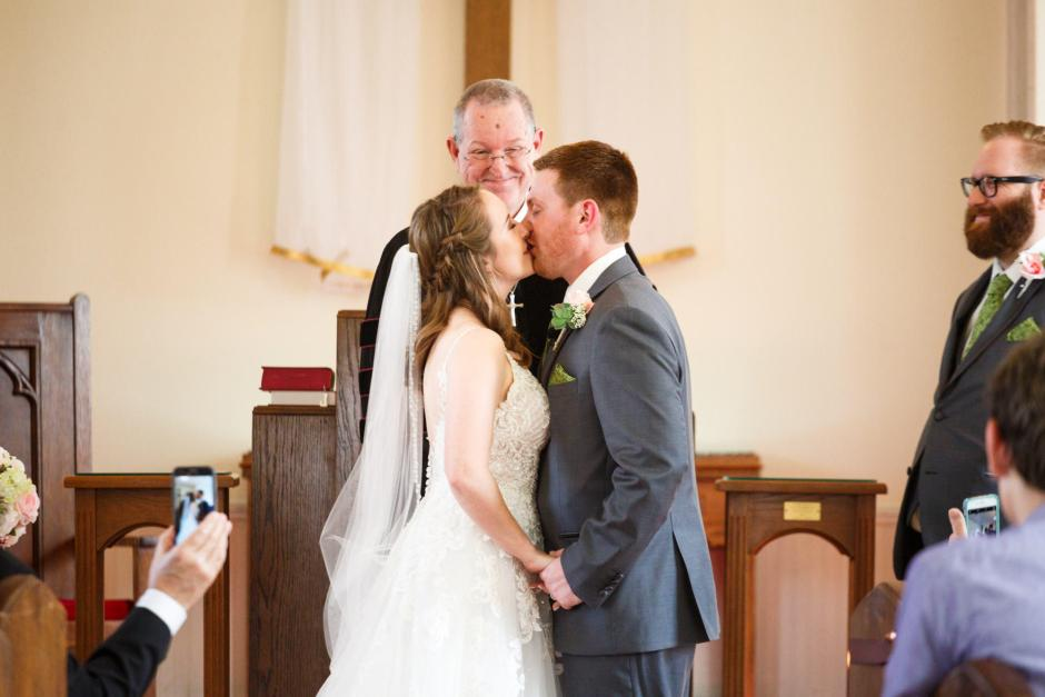 Joshua and Brittany Wedding - Bride and groom's first kiss at Hyde Park Presbyterian Church in Austin, TX.