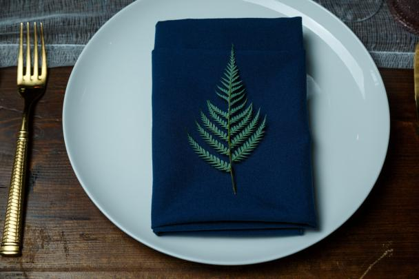 Mike and Kathie's Palm Door on Sixth wedding place setting featuring fern leaves.