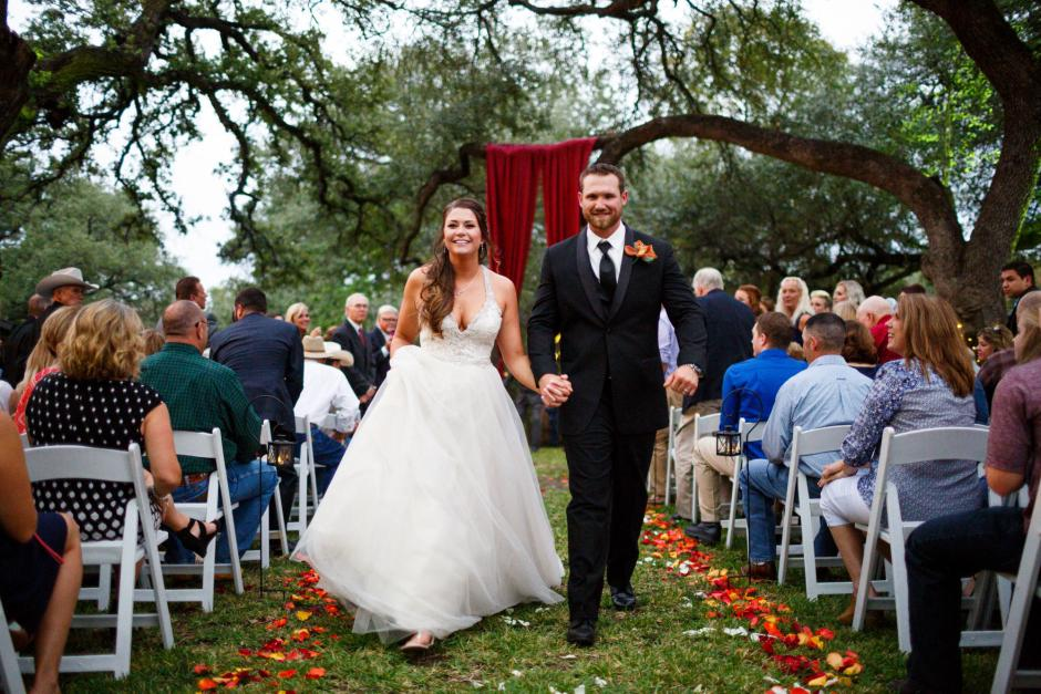 Bride and groom leave from their wedding ceremony under the huge oak trees at Cathedral Oaks in Belton, Tx.