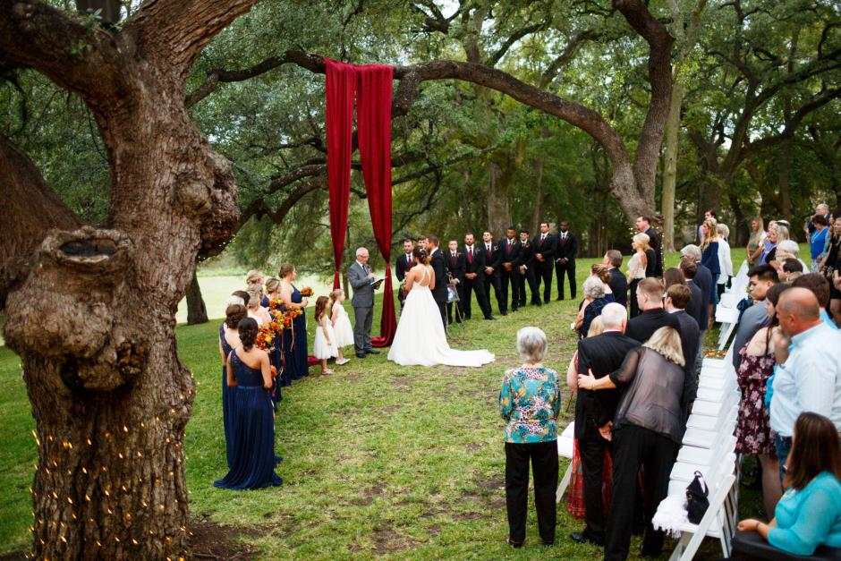 Bride and groom stand at the alter under the large oak trees at a Cathedral Oaks Wedding in Belton, Tx