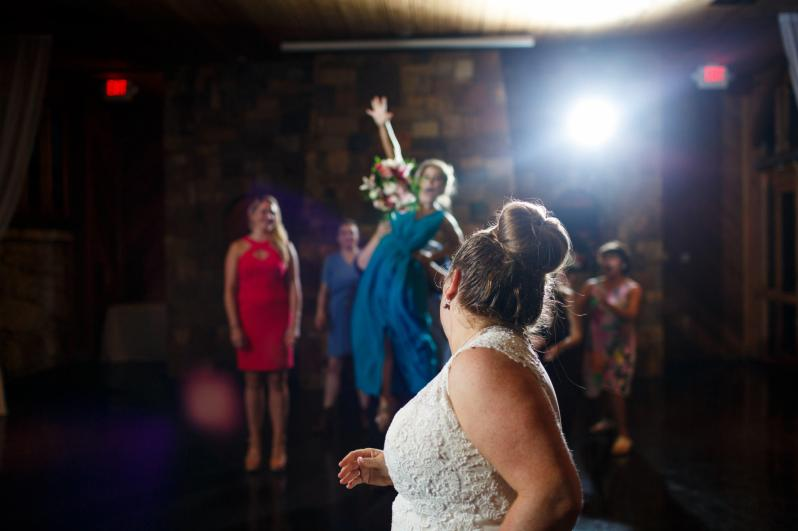 Bride tosses her bouquet at her The River Venue wedding reception in New Braunfels TX.
