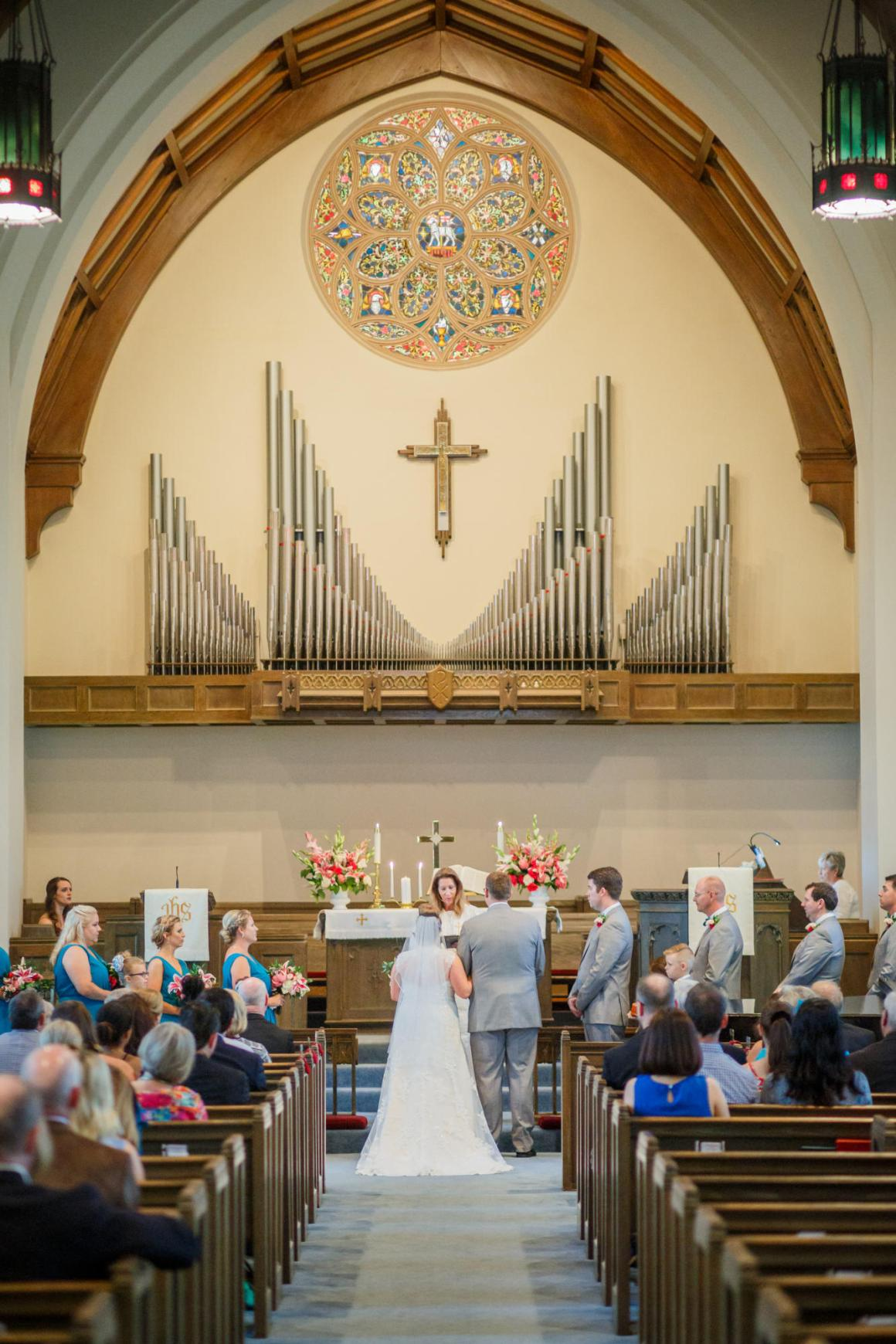 Bride and groom stand at the alter in United Methodist Church in Seguin Texas with large organ in the background.