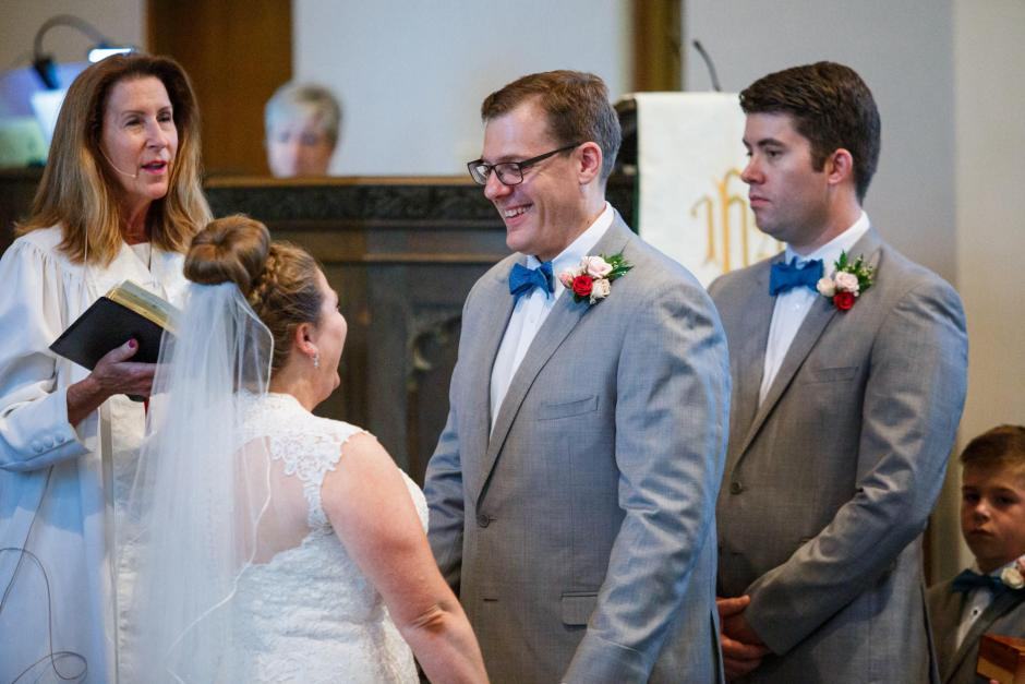 Groom smiles at bride during their United Methodist Church Wedding ceremony in Seguin Texas.