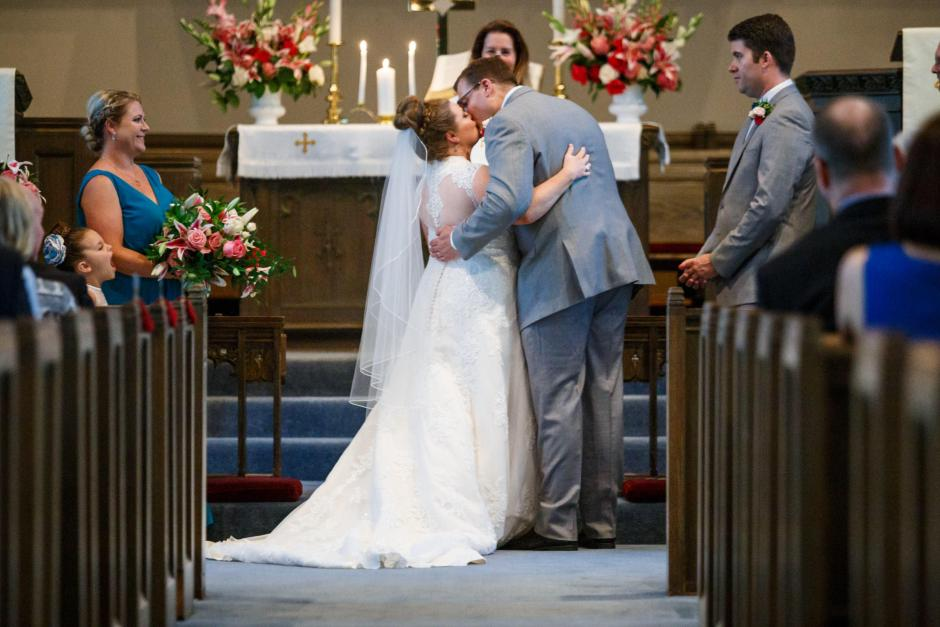 Bride and groom have their first kiss during their United Methodist Church Wedding ceremony in Seguin Texas.