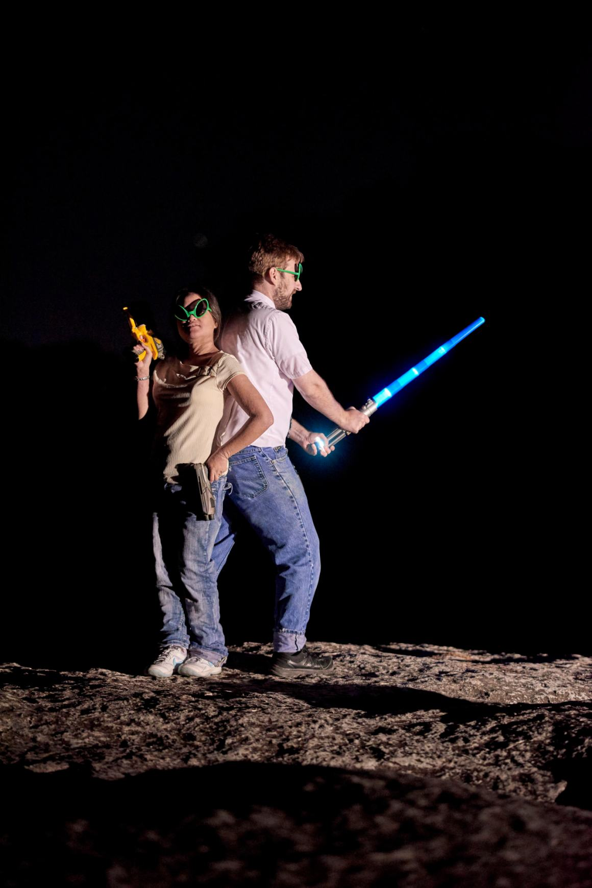 Fun geeky star wars inspired fun during an engagement session under the stars. James holds a toy light-saber and Nicole has a prop blaster.