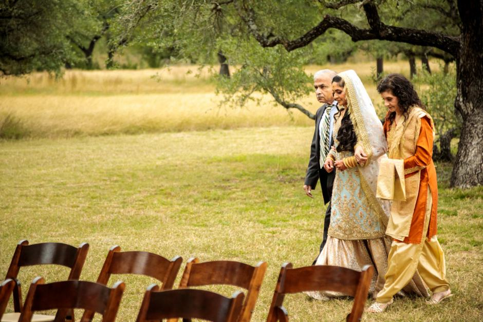 Bride is walked in to her outdoor wedding ceremony by her parents - Heart of Texas Ranch Wedding in Marble Falls Texas - Indian-Christian Fusion Wedding
