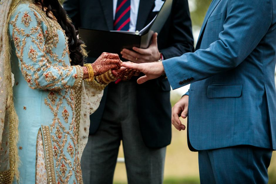 Bride places the wedding ring on the groom's finger during their Heart of Texas Ranch wedding in Marble Falls Texas - Indian-Christian Fusion Wedding