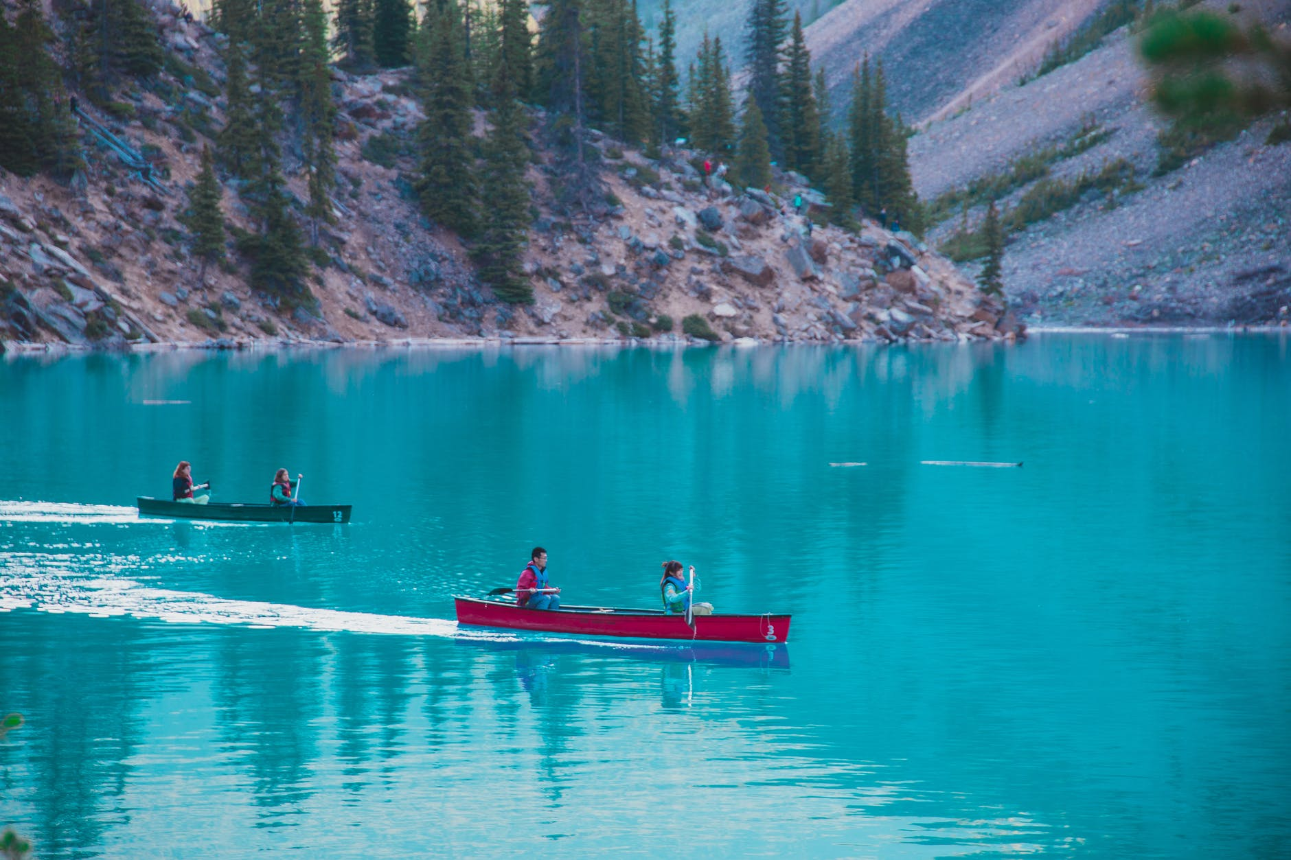 people floating in canoes on azure lake