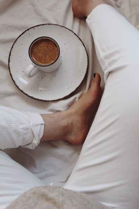 unrecognizable woman drinking hot beverage on bed in morning