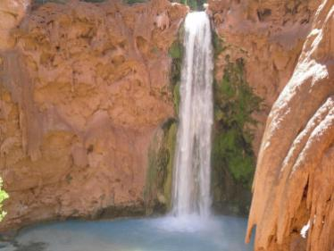 Tall waterfall cascades into pool of light blue water