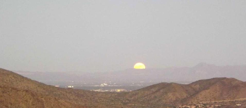 Full moon rising over desert hills