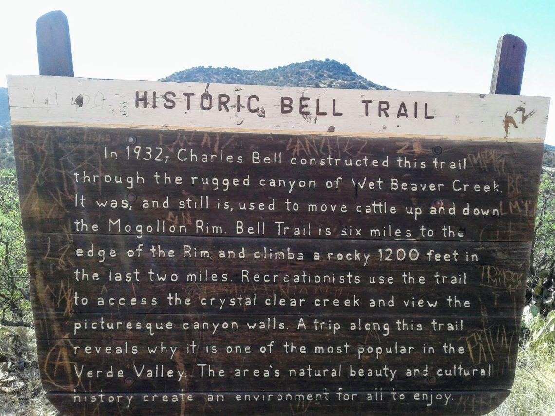 Weathered brown and yellow sign with title Historic Bell Trail followed by brief history