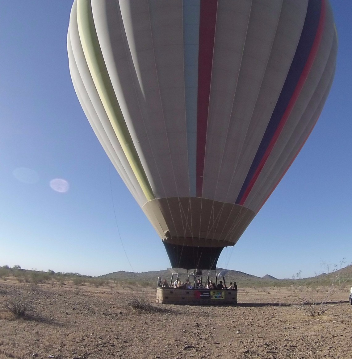Hot air balloon resting on mostly barren desert