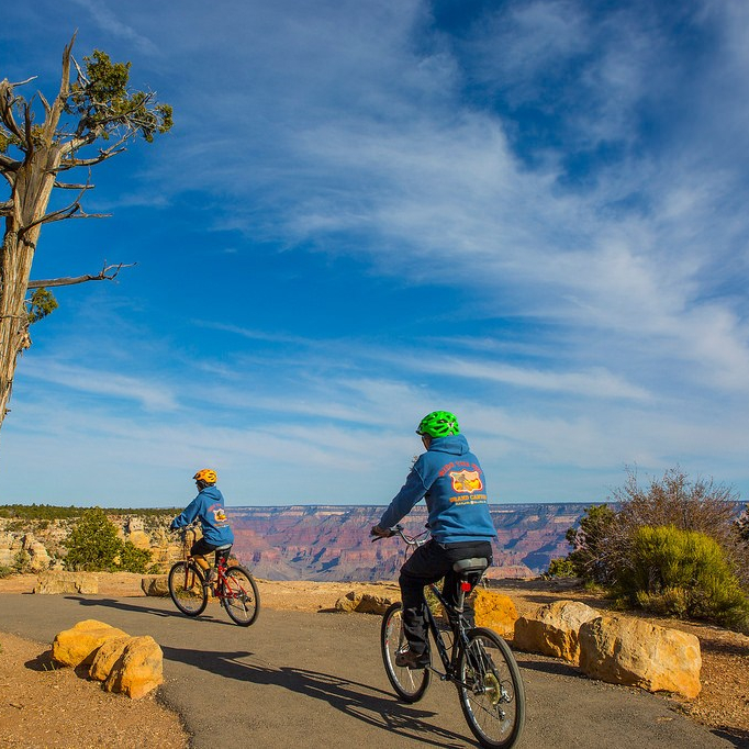 Two people bicycling on paved trail along rim of Grand Canyon