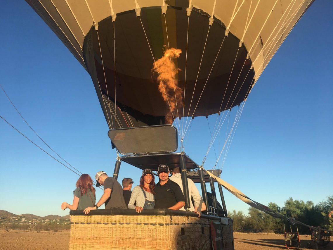 People in passenger basket beneath hot air balloon