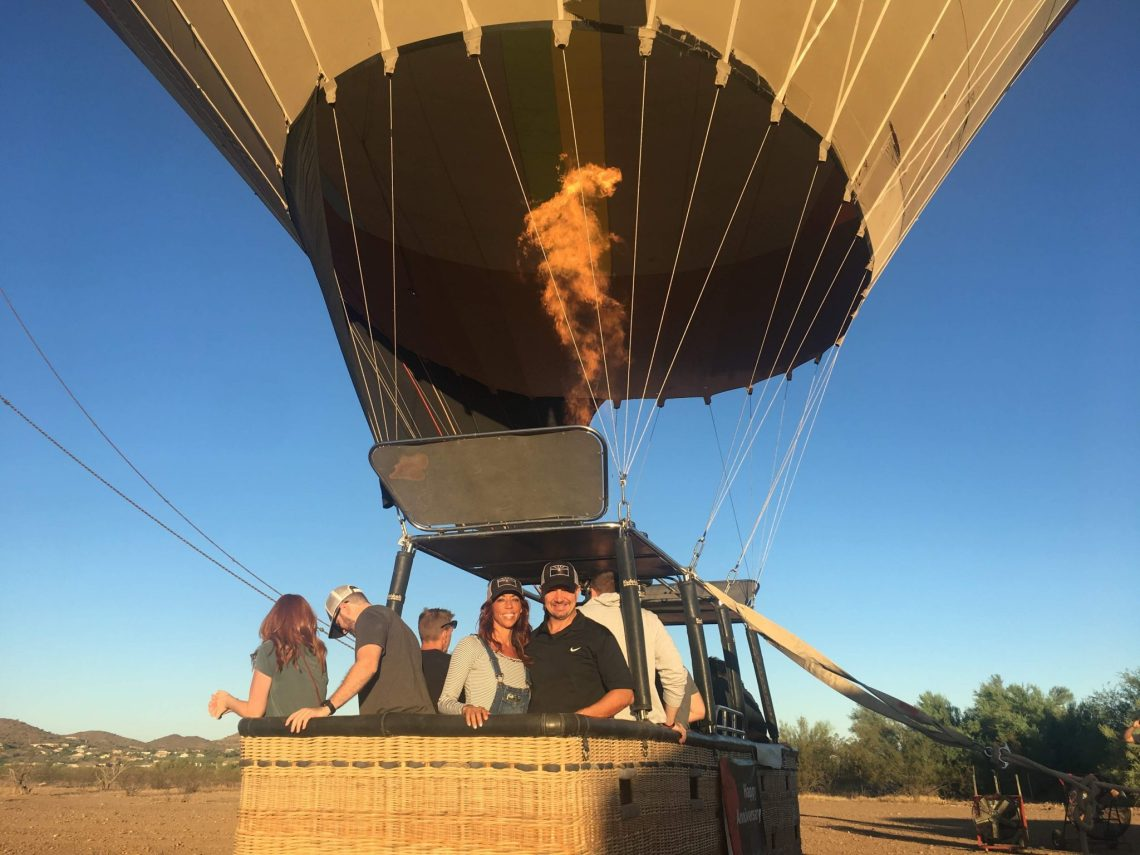 People in passenger basket beneath hot air balloon