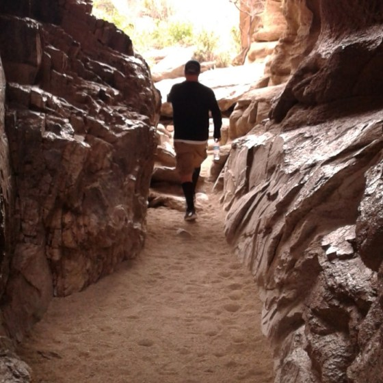 Man hiking through tunnel through boulders