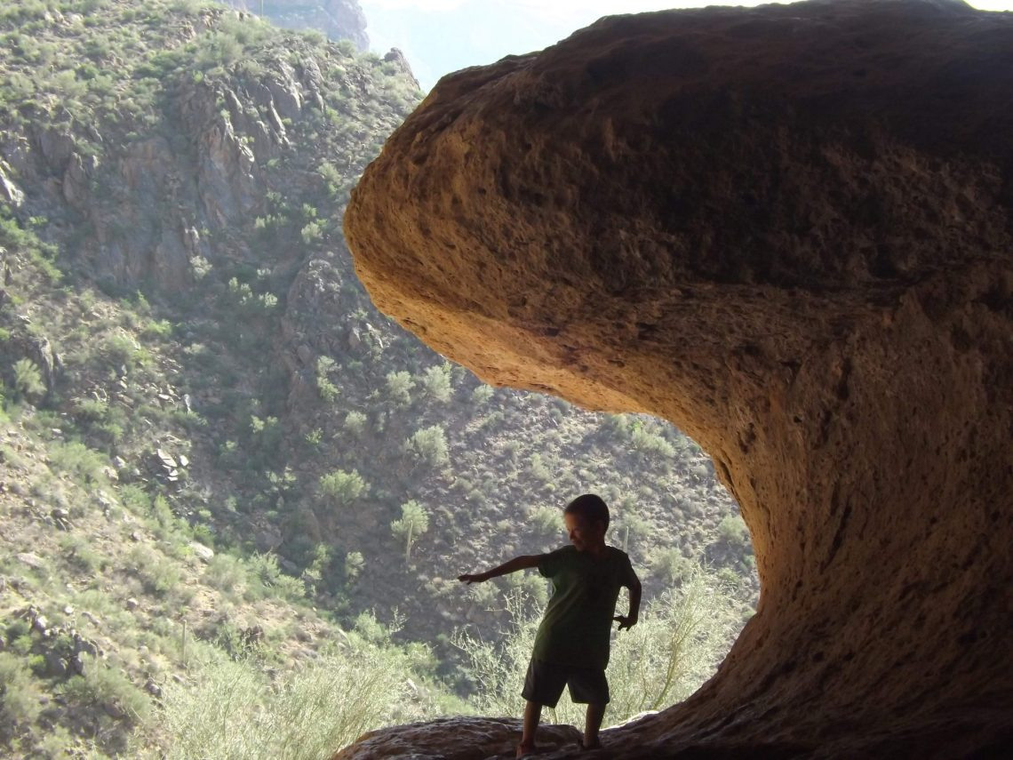 little boy strikes a surfing pose at the Wave Cave