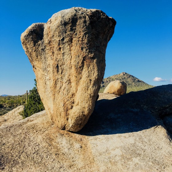 Large top-heavy rock balancing on a slope