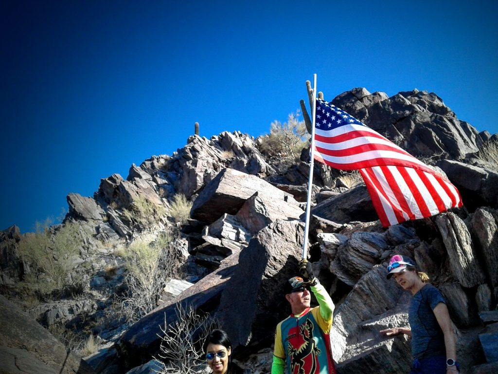 Man holding flag high overhead with rocky mountain behind him