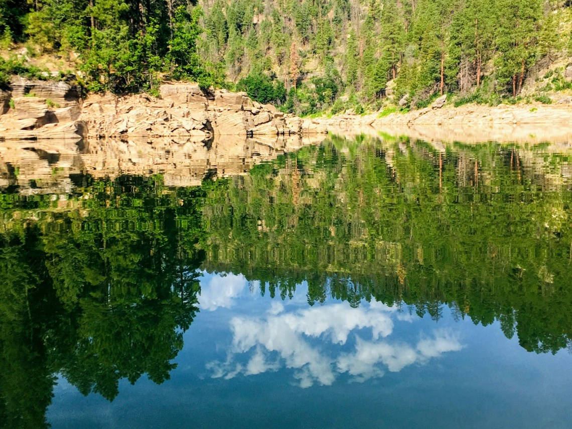 Glassy calm water of Blue Ridge Reservoir reflects the scenic trees and sky above