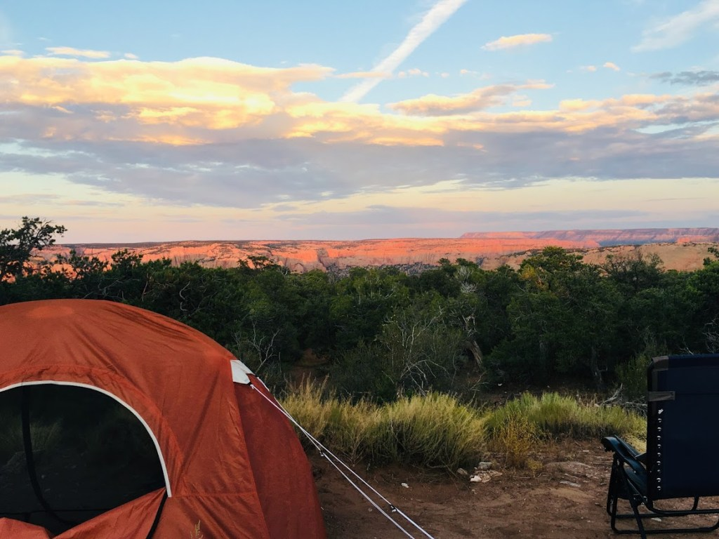 Tent in foreground with spectacular view out over a sunlit canyon