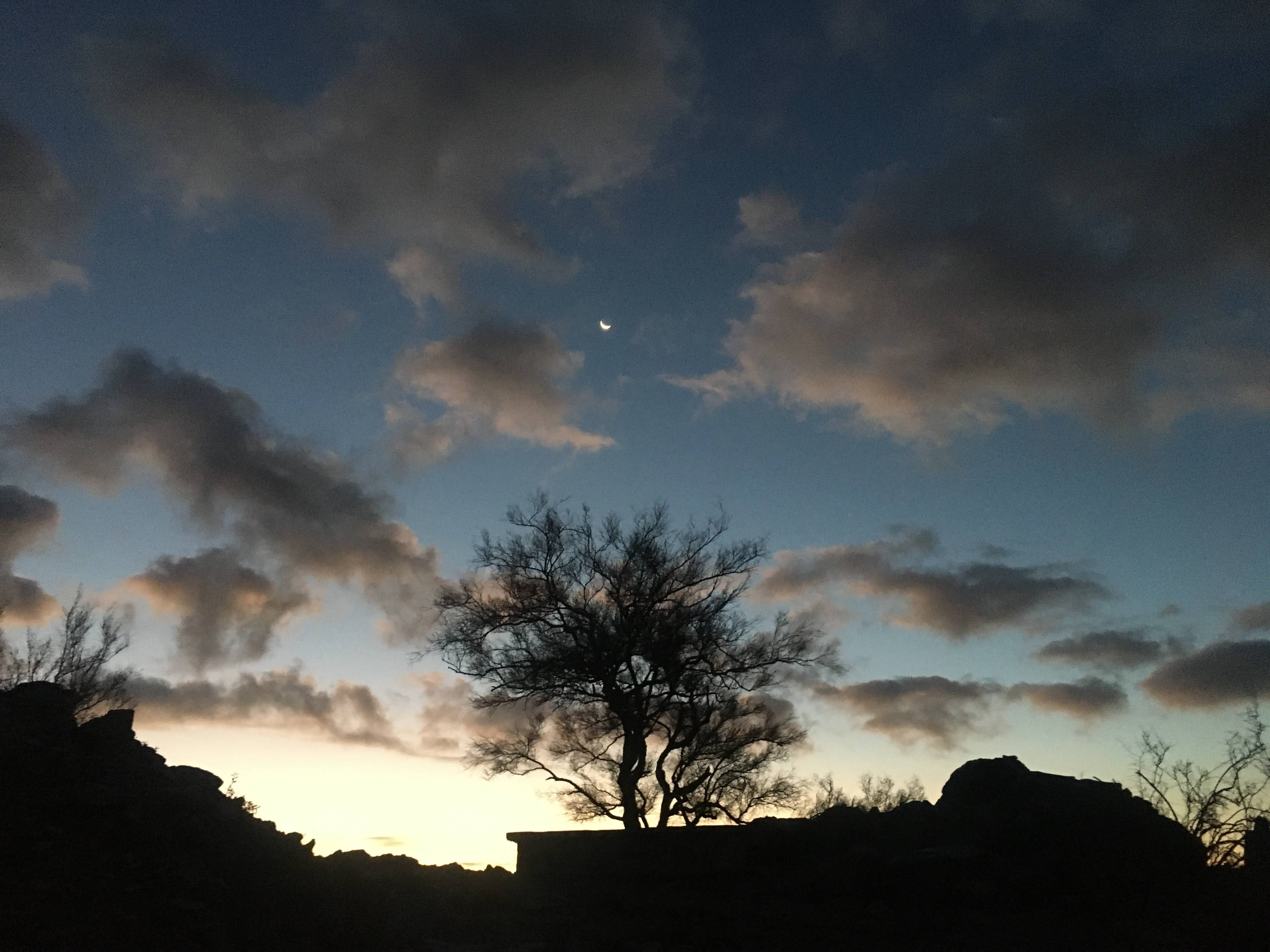 silhouette of mountain with partly cloudy sky in background