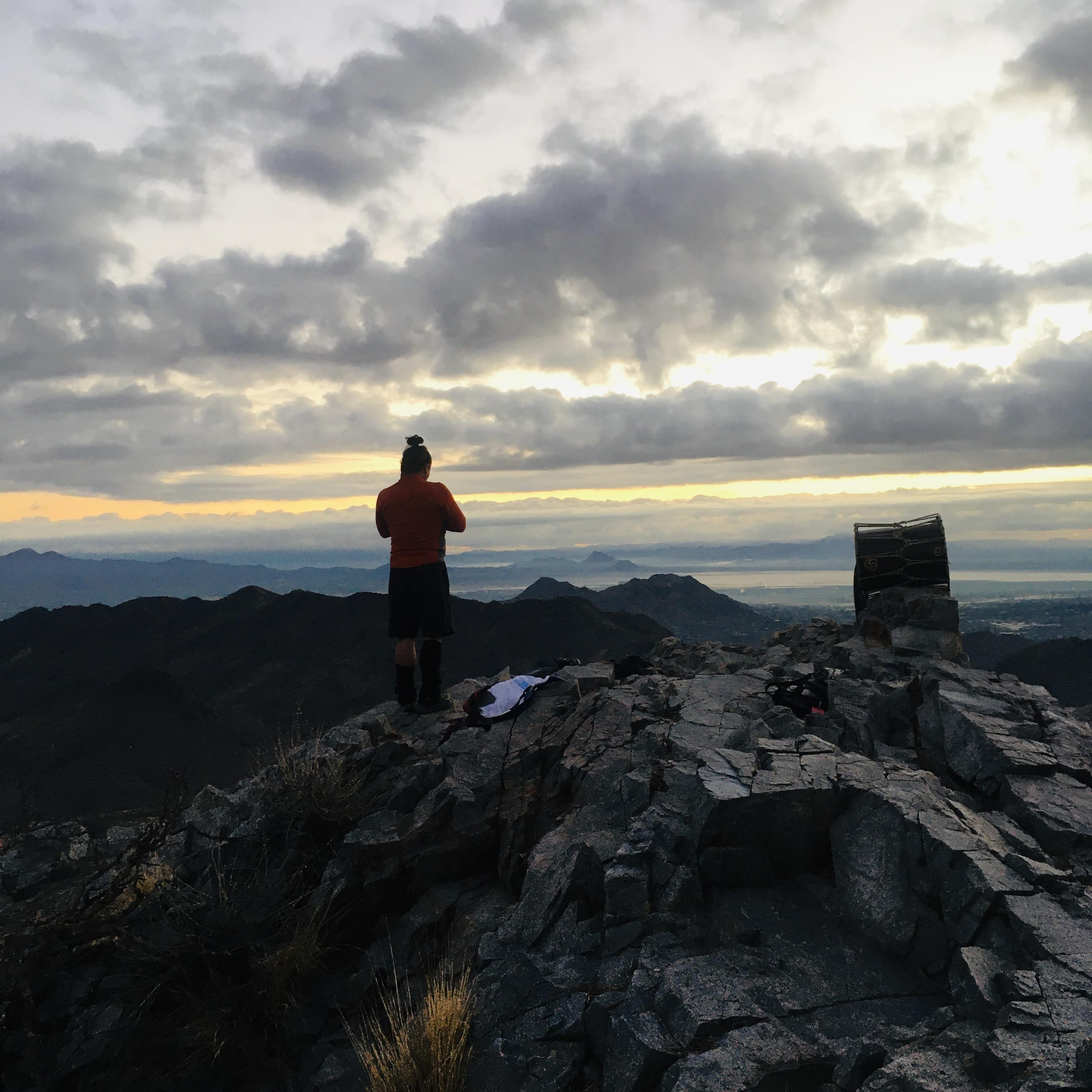 Man on top of mountain as sun rises in background