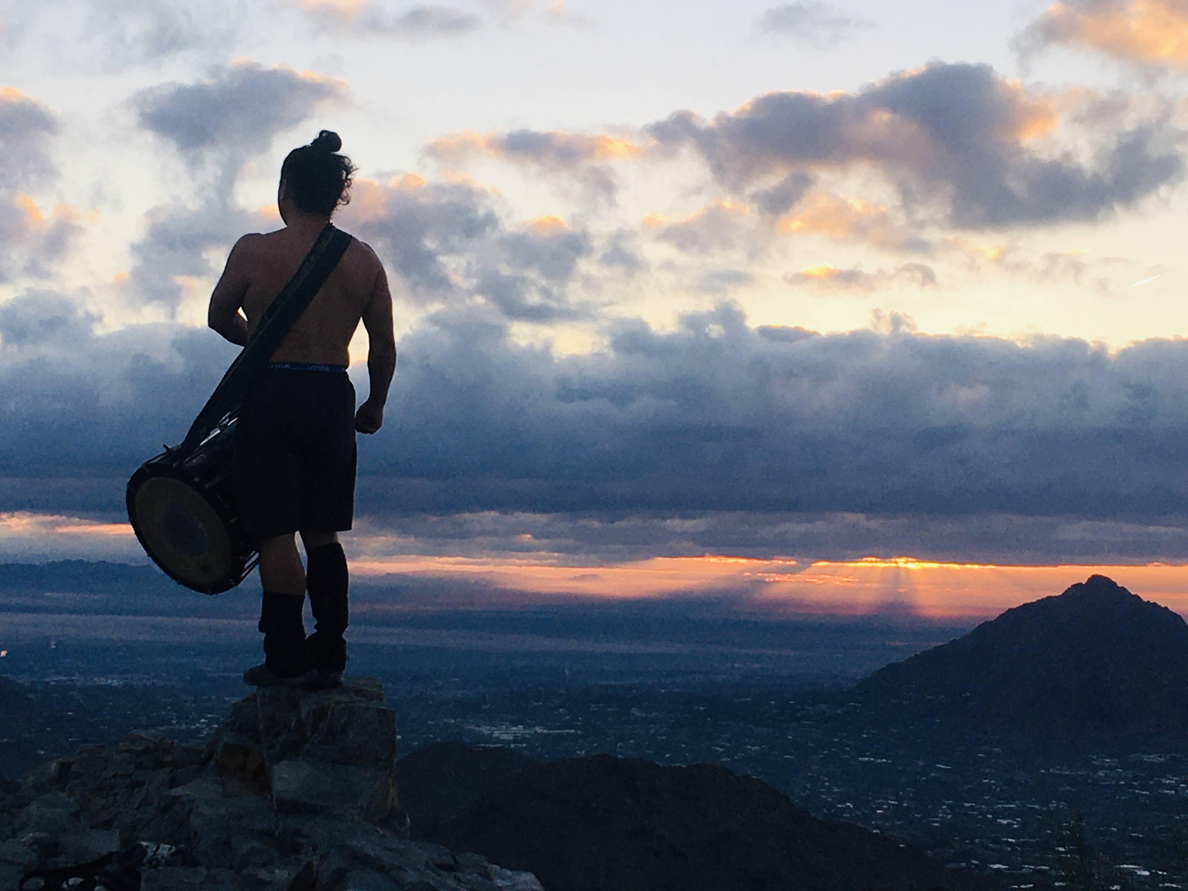 man playing drum on top of mountain